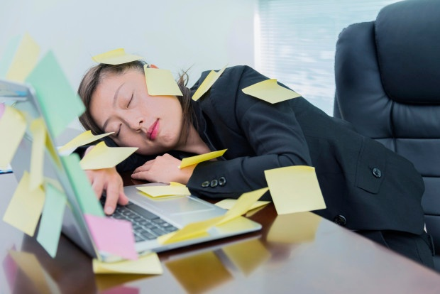 Businesswoman sleeping in office, with many adhesive notes on laptop.